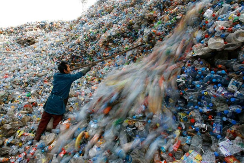 A worker is sorting plastic bottles that pile up into mountains